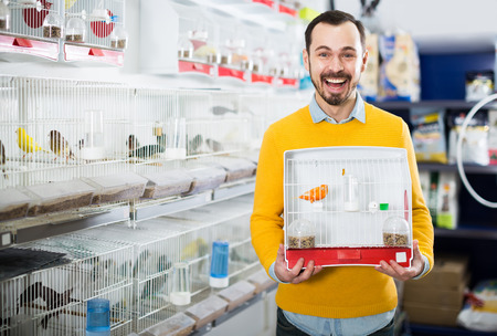 Young man excited about the purchase of selected bird canaries in the store Stock Photo