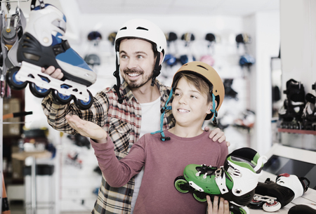 Young spanish father and son deciding on new roller-skates in sports store
