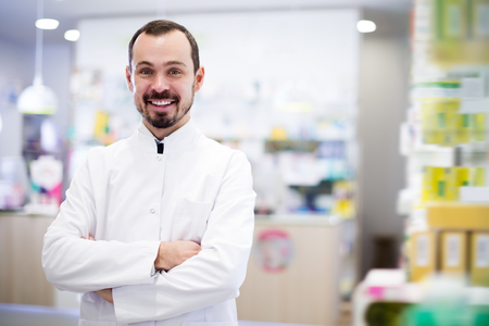 Handsome pharmacist showing assortment of drugs in pharmacy Stock Photo