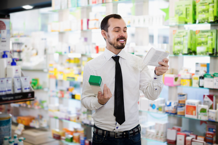 Positive male customer looking rows of drugs in drugstore Stock Photo