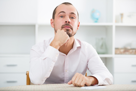 Confused young married man reading documents at his workplace Stock Photo