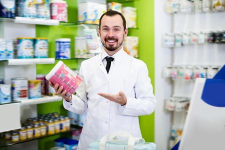 Ordinary male pharmacist suggesting useful drug in pharmacy