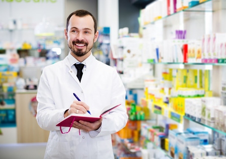 Smiling adult  pharmacist writing down assortment of drugs in pharmacy Фото со стока