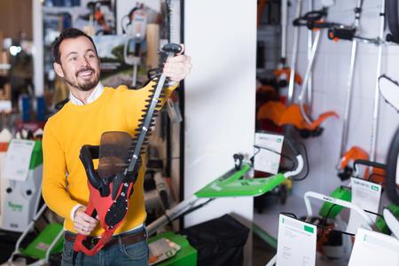 Happy adult guy deciding on best hedge cutter in garden equipment shop