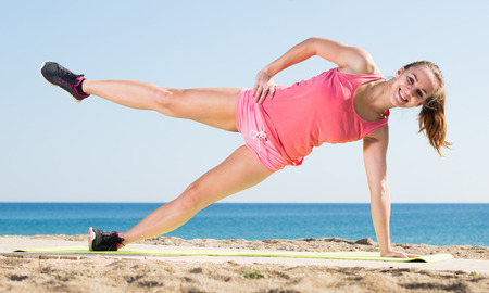 Pretty young sporty woman exercising at sea beach Stock Photo