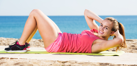 Young cheerful caucasian woman doing yoga at seaside on a sunny day