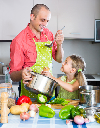 Smiling man and cute little girl cooking vegetables in the kitchen at home