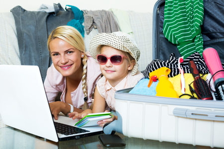 Attractive blonde mother and little girl with luggage browsing web. Focus on the girl Stock Photo