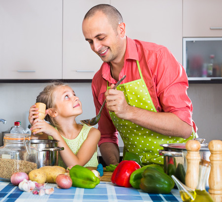 russian girl helping father to prepare dinner indoors