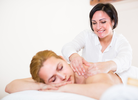 Adult masseuse is doing relaxing massage shoulder area for young woman in spa salon.