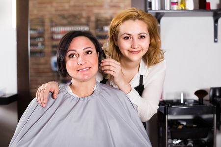 Mature woman likes very much her hairdress in hairdressing salon.