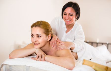 Young female is happy with procedure massage in beauty parlor and waiting for using bamboo sticks for massage.