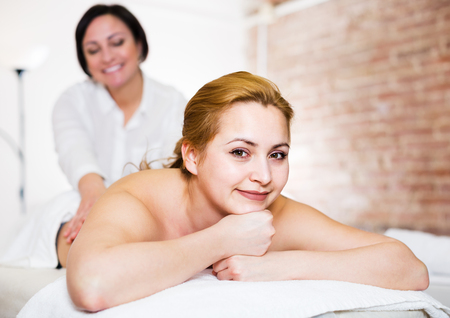 Adult massagist massaging back and loin area of young smiling woman in massage salon Stock Photo