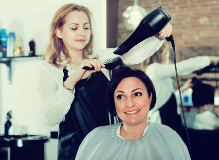 Young satisfied pleasant  hairdresser styling and drying hair with fen and brush of women in beauty salon