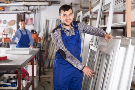 Glad young production workers in coverall with different PVC windows and doors Stock Photo