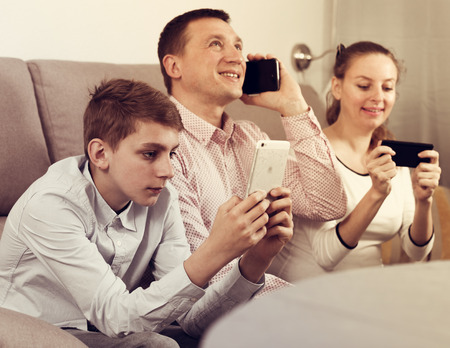 Parents and son happy to play with mobile phones together at home Stock fotó