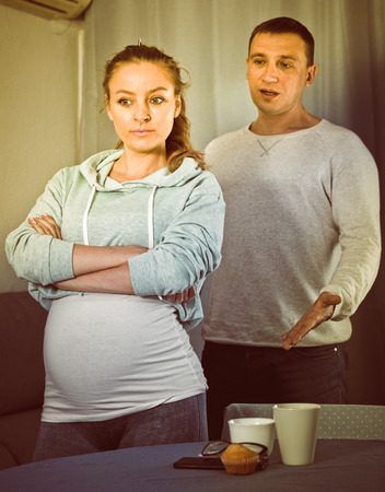 Husband and pregnant wife having disagreement with each other at home