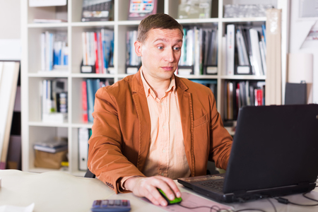 Man working with documents and laptop in agency office