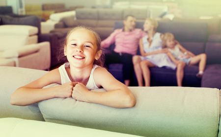 Child is happyning of new sofa in furniture store. Stock Photo
