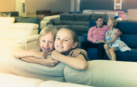 Portrait of smiling sisters are standing near new sofa in furniture store Stock Photo