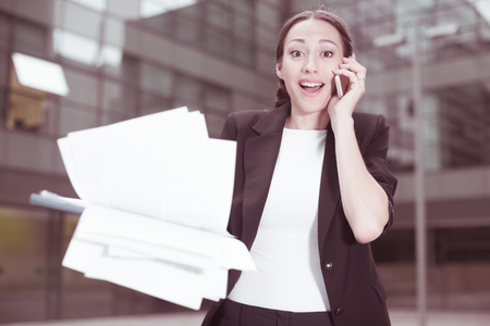 Female manager is happy after agreed about the successful transaction by phone outdoors.