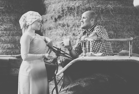Cheerful young woman chatting with smiling mature farmer with glass of milk in tractor in hay hangar. Focus on man
