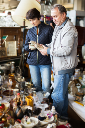 Adult woman and her husband are visiting the market of old things and shopping outdoors Stock Photo