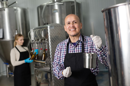 Mature cheerful man wearing the uniform standing among a brewery stainless equipment