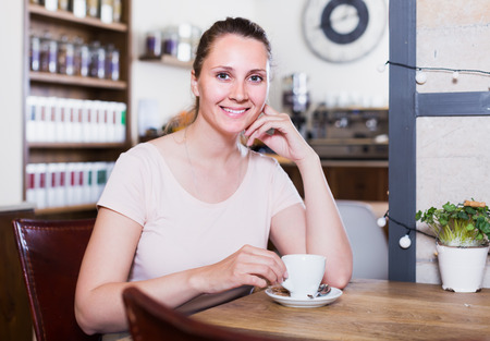 young smiling woman resting alone at the table in cafe and drinking coffee Stok Fotoğraf