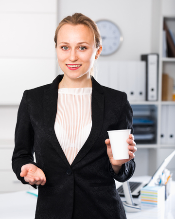 Young female drinking water and working in the office