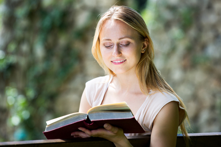 Closeup on positive blond young woman reading book in park on sunny day Stock Photo