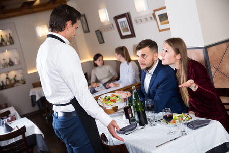 Dissatisfied family couple talking to apologetic waiter, dissatisfaction with food