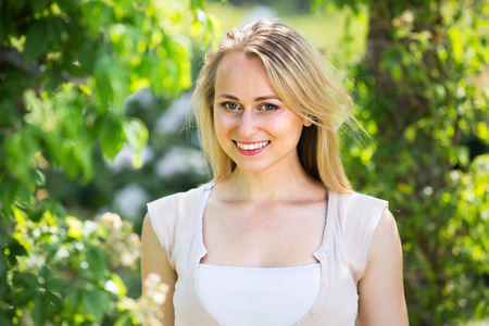 сloseup of сheerful young woman standing outdoors on sunny day