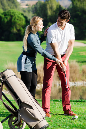 Positive young woman golfer training man to play golf and hit ball correctly