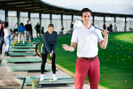 Young man golfer propelled ball successfully at golf course