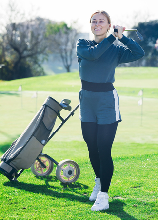 Smiling female golf player made successful hit at golf course