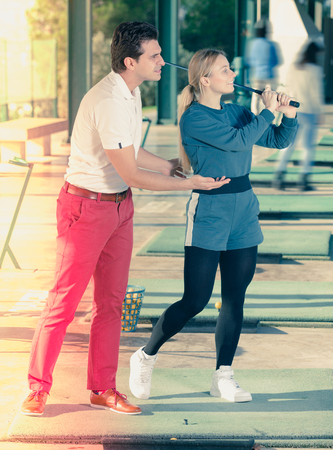 Cheerful man golf trainer showing female player how to hit ball rightly Stock Photo