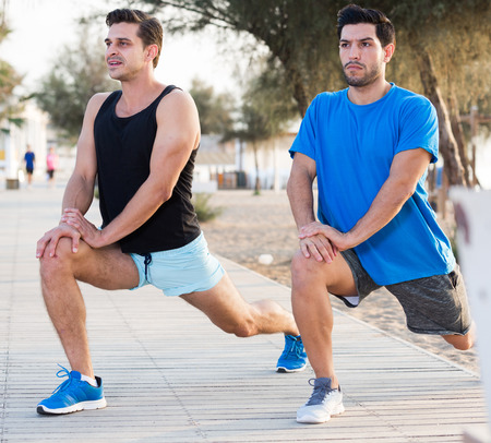 Smiling adult men are warming-up in the park near beach. Stock Photo