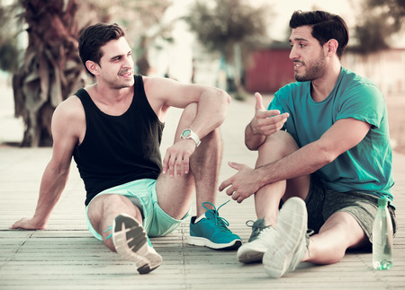 Two male friends are resting after training and talking about lifestyle in the park near beach