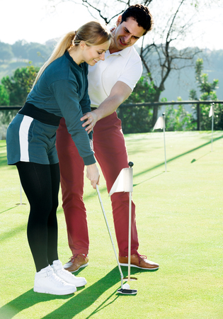 Male golf trainer showing female player how to hit ball rightly