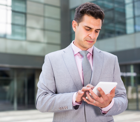 Businesswoman holding and using touchscreen phone outdoor Stock Photo