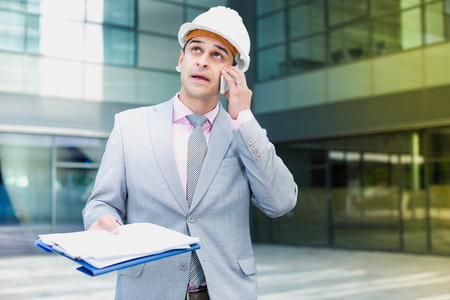 Surprised and shocked businessman holding documents and having phone conversation outdoor