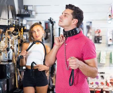 couple of shoppers choosing collar with thorns and leather lash