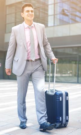 Portrait of positive confident businessman walking with travel bag