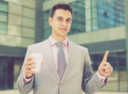Businessman pressing imaginary button on large plant background Stock Photo