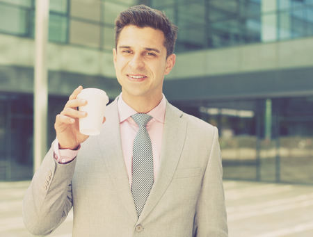 Portrait of young successful businessman drinking coffee near large factory