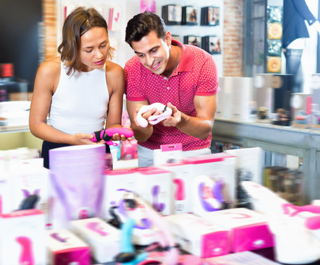 Glad  positive smiling couple of woman and man buyers choosing color sexy toys in the sex shop 스톡 콘텐츠