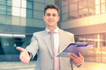 Successful businessman standing outdoor with open hand ready for handshake Stockfoto