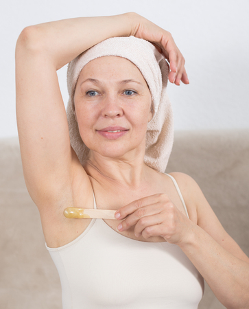 Mature woman getting body hair removed at home Stock Photo