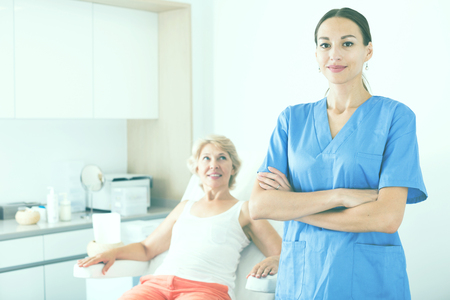 Portrait of professional cosmetician standing in medical esthetic office Stock Photo